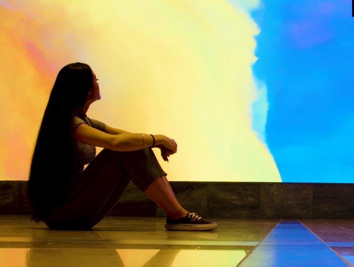 A woman sitting in front of the videowall.
