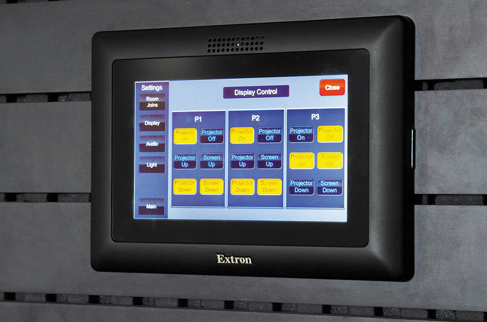 Both staff members and clients use an Extron TLP Pro 520M TouchLink Touchpanel to select among the room's predetermined states, which include control of audio, projection systems, and lighting.
