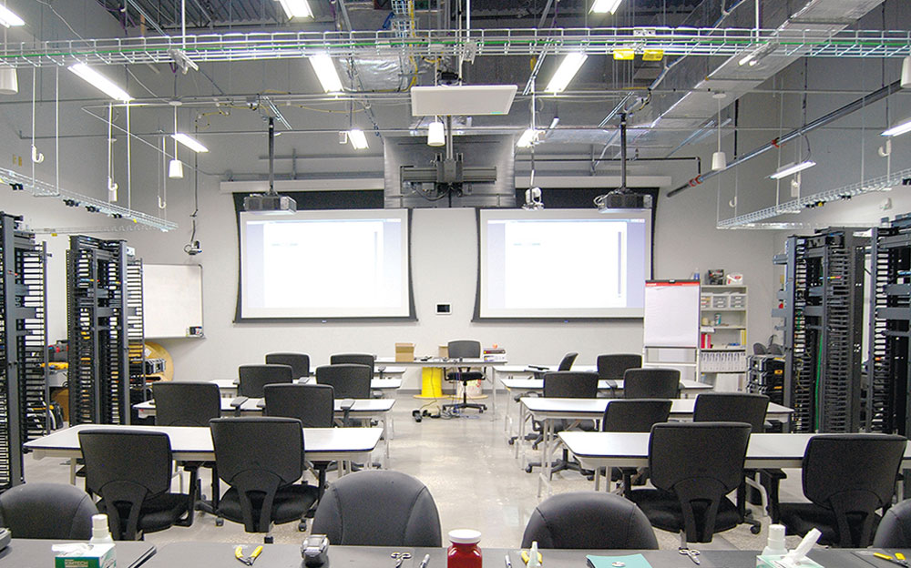 AV in training classrooms allows students to view table-top demonstrations on the projection screens without leaving their seats. Ceiling-mounted flat panel display faces instructor