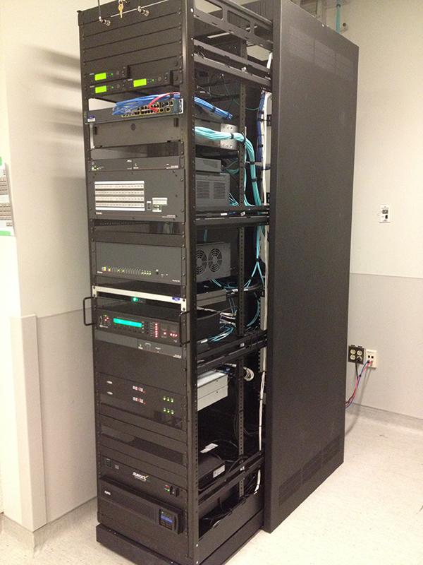 The FOX Matrix 3200, sound system, and other AV equipment are rack-mounted in a nearby space.
