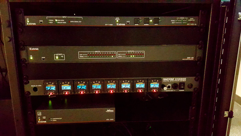 The rack in the control room holds the Extron extenders and audio products, as well as the shared resources.
