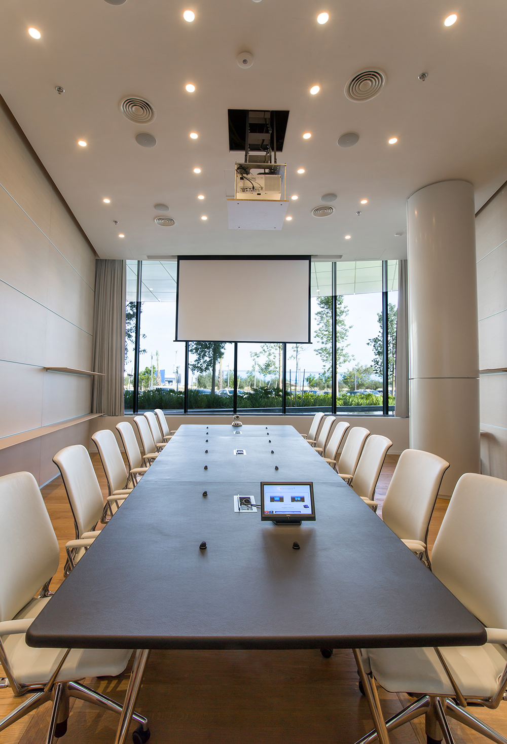 In the boardroom, Extron DTP T USW 233 switchers mounted beneath the table send signals to the matrix switcher.