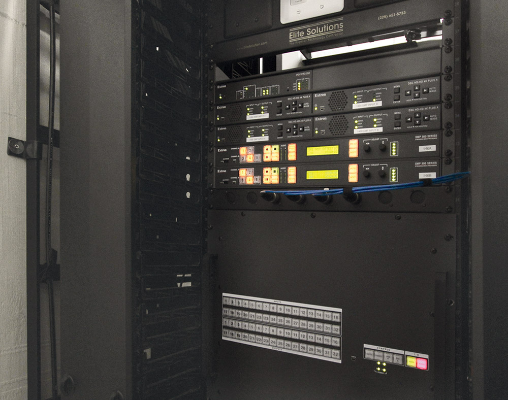 An equipment closet housing AV system central switching, scaling, streaming, and control equipment