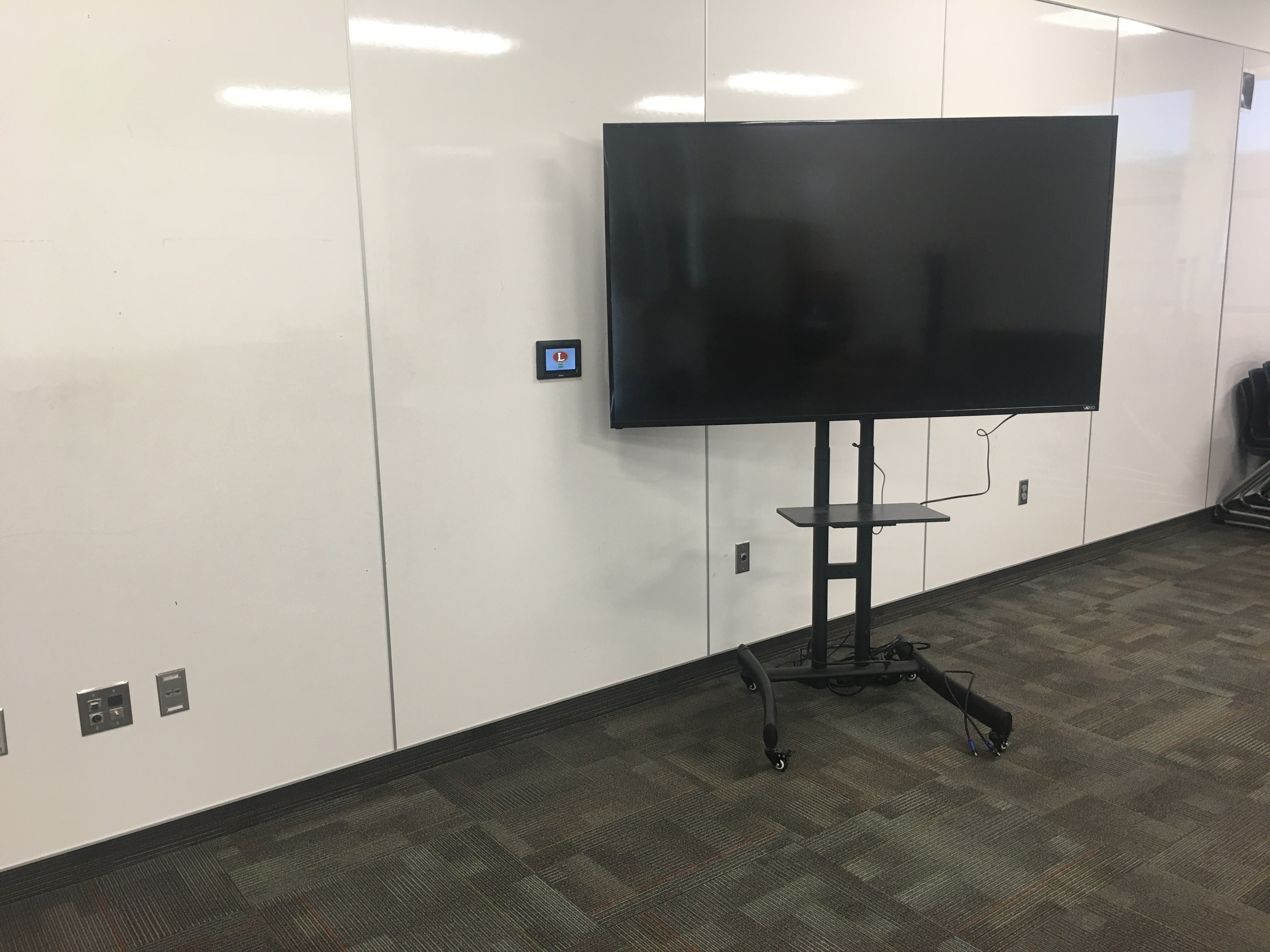 A portable display cart connected via wallplate