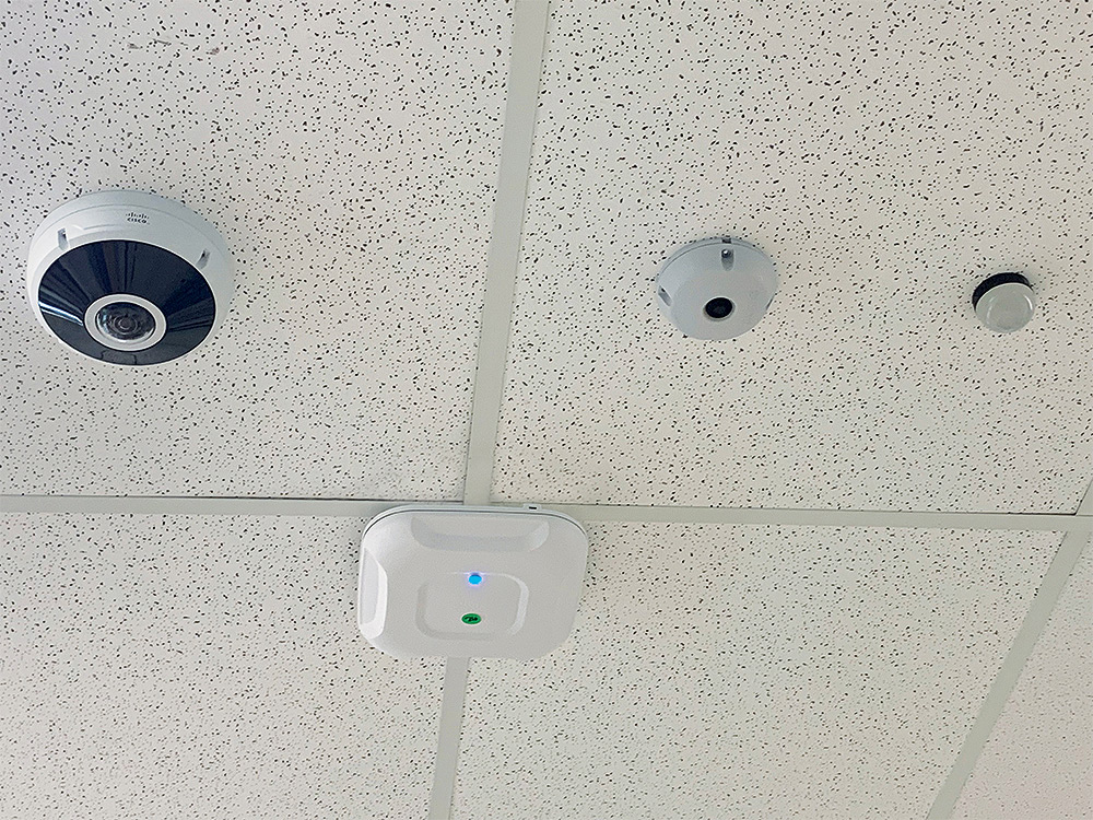 Classroom surveillance camera and Recording-in-Progress light share ceiling space with motion sensor and WiFi access node.
