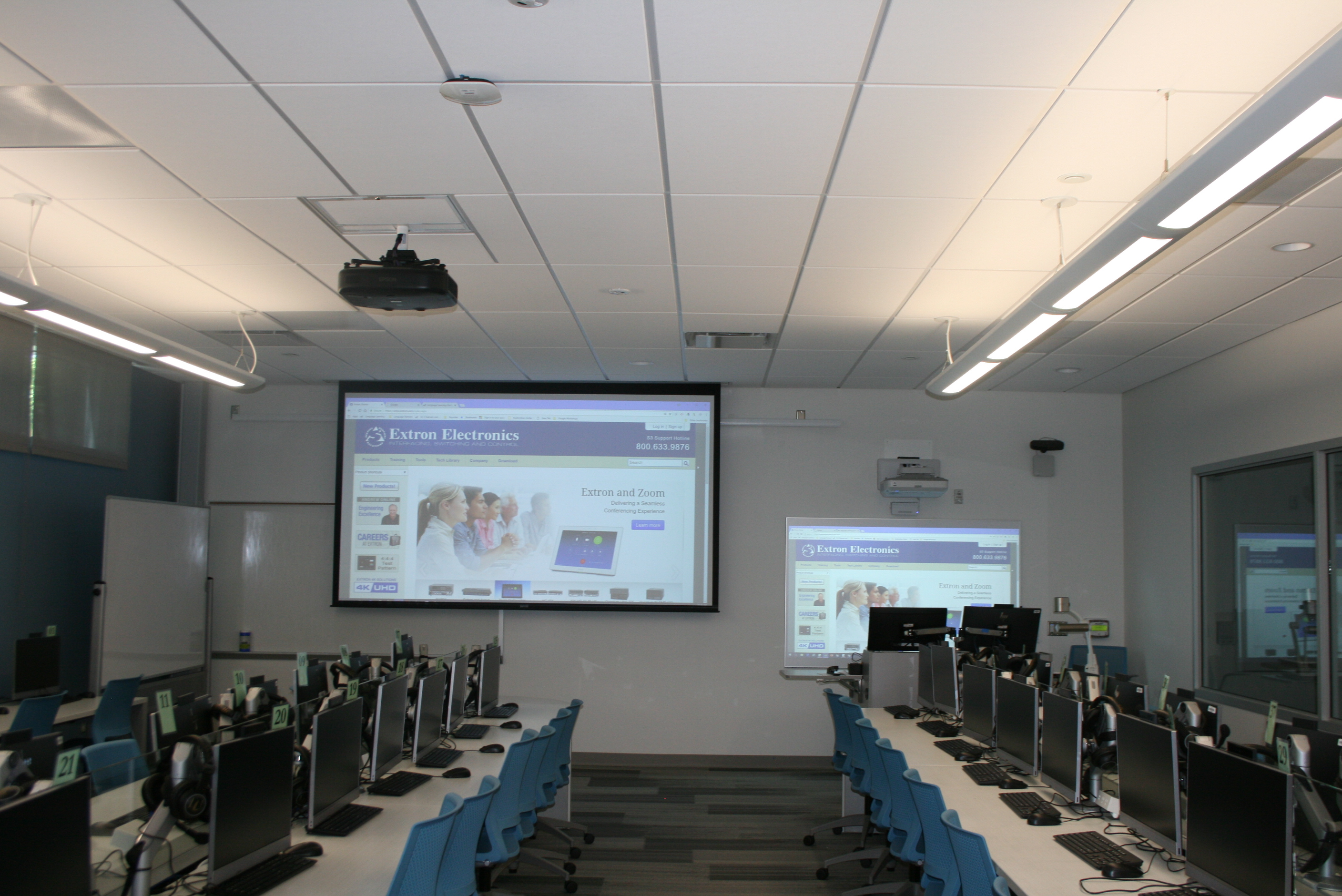 Classroom with a projection screen in front and to the side of the whiteboard