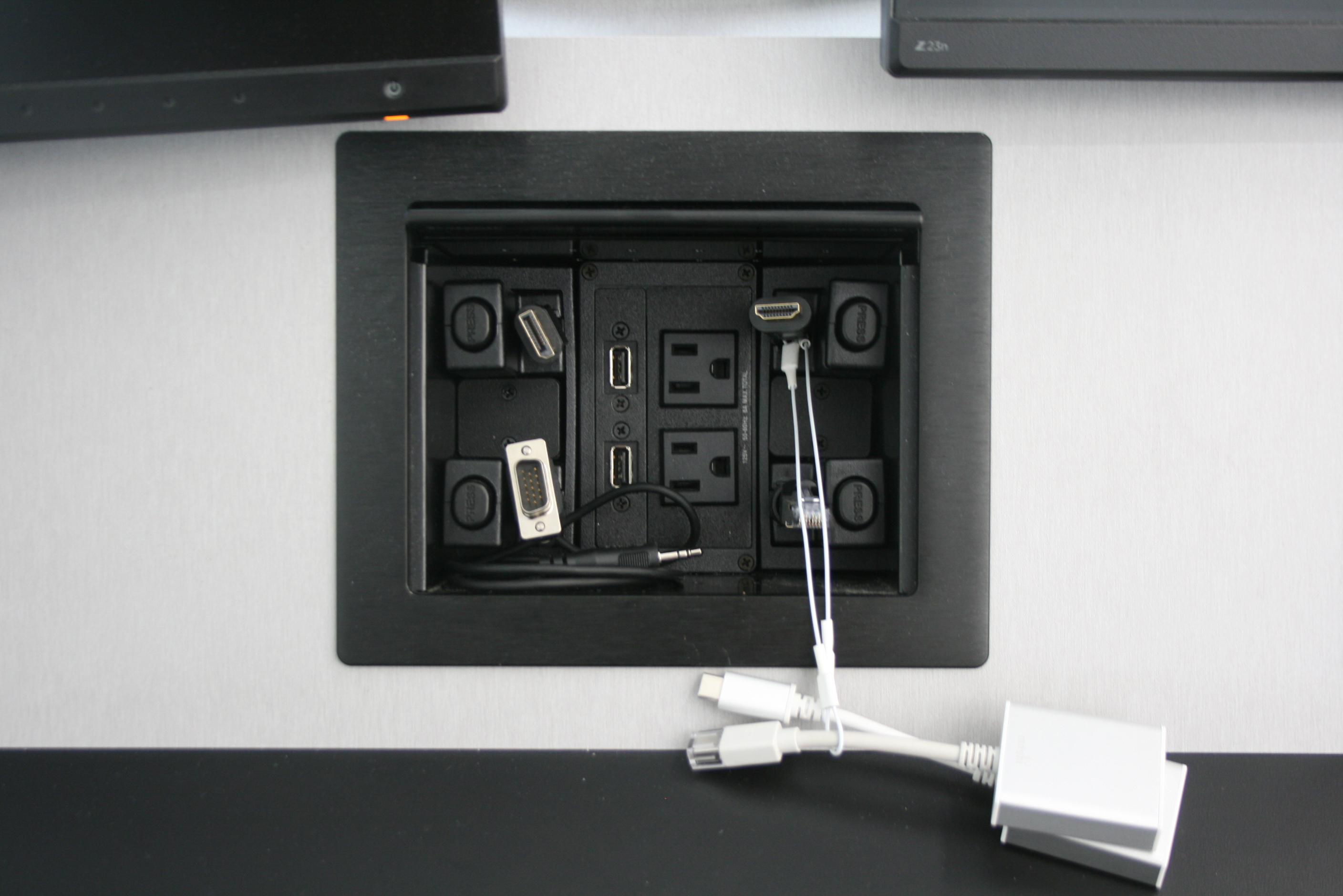 Instructors can connect a portable devices at the teaching station using cables fed through an integrated Extron Cable Cubby<sup>®</sup> enclosure paired with Retractor<sup>®</sup> cable retractiong and management modules.
