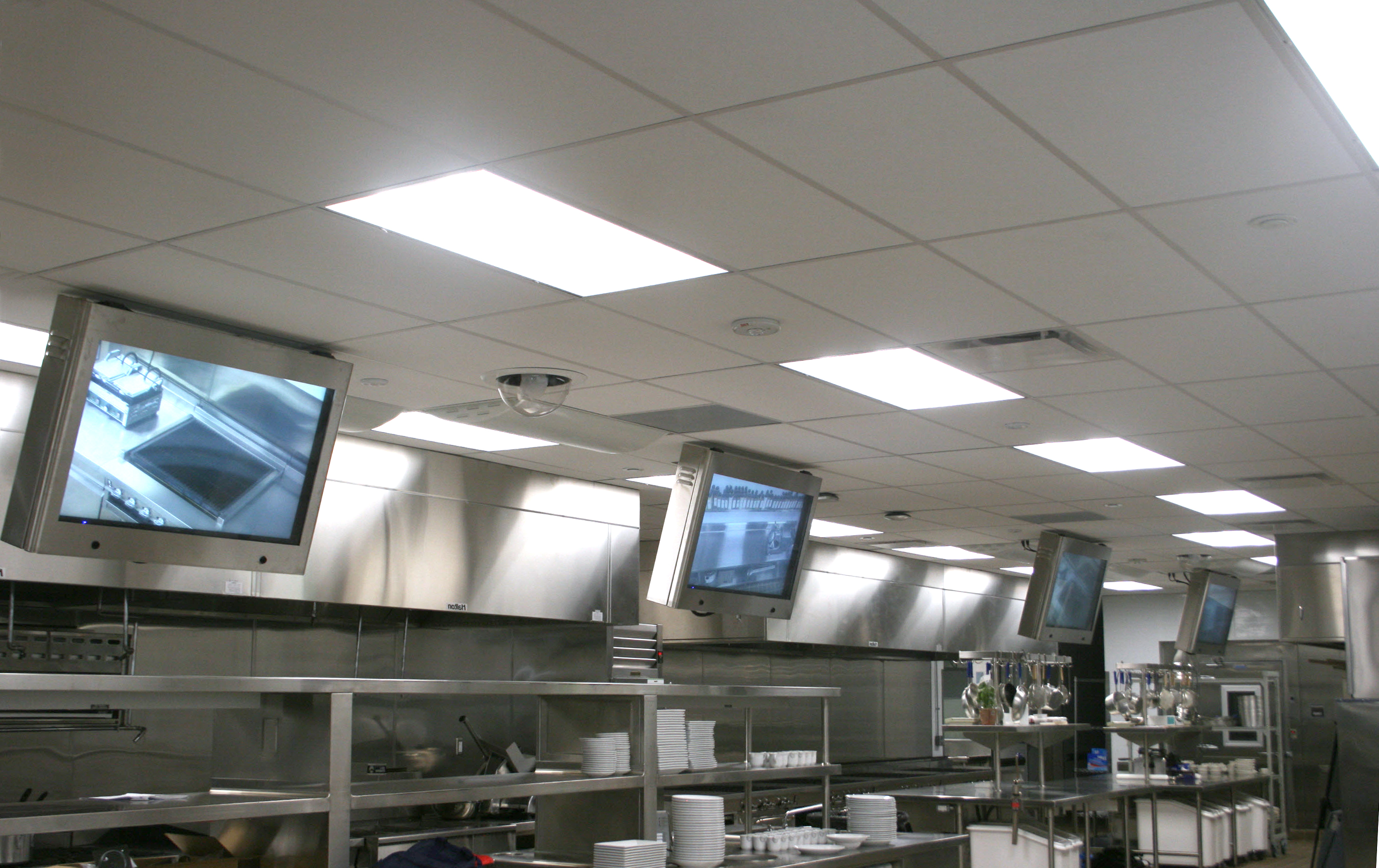 Flat panel displays that are angle-mounted above kitchen workstations