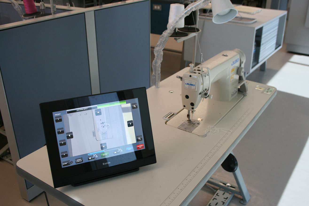 The control interface is customized to enable display of each workstation for activities such as a sewing technique demonstration in this fashion design classroom.