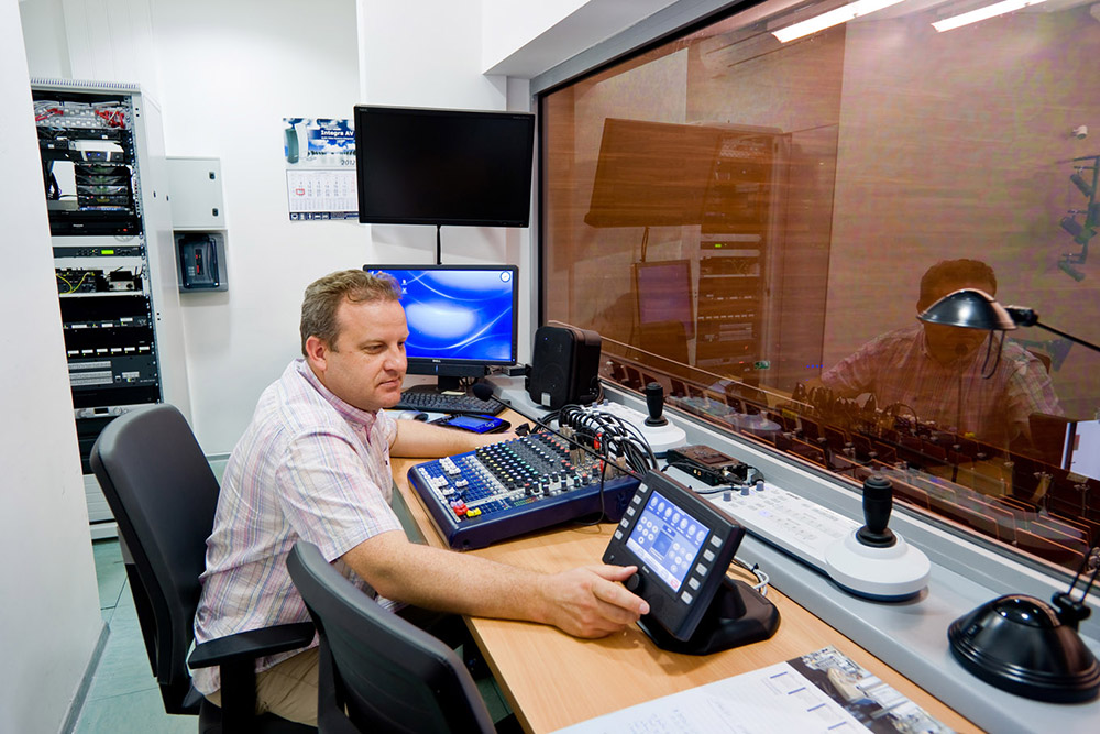 An Extron TouchLink touchpanel helps simplify remote AV system operation from the auditorium's control room.