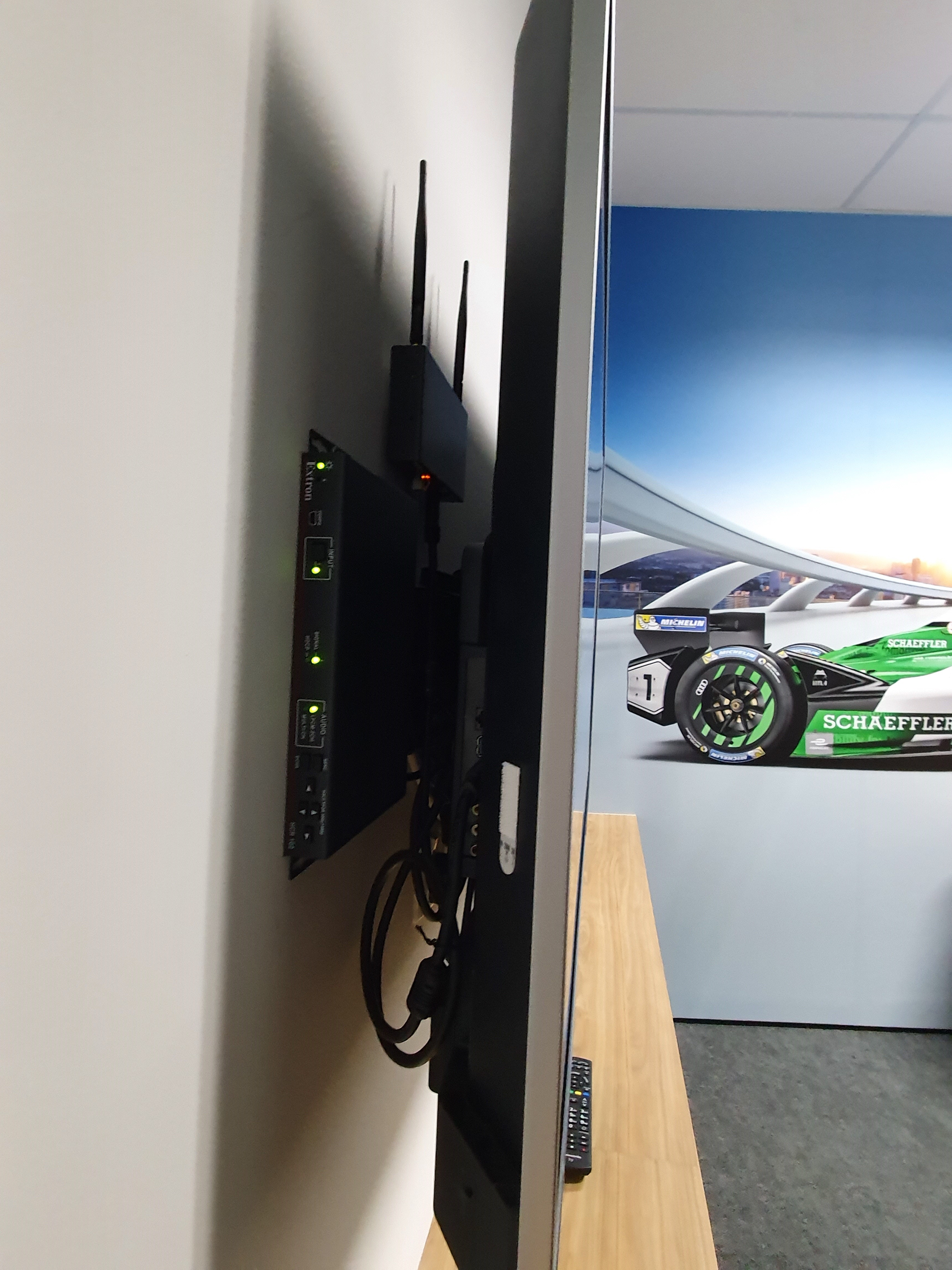 To achieve a sleek and modern environment in board rooms, auditoriums, and think tanks, the low-profile Extron HC 404 collaboration receiver and ShareLink wireless gateway are installed behind the flat panel display.