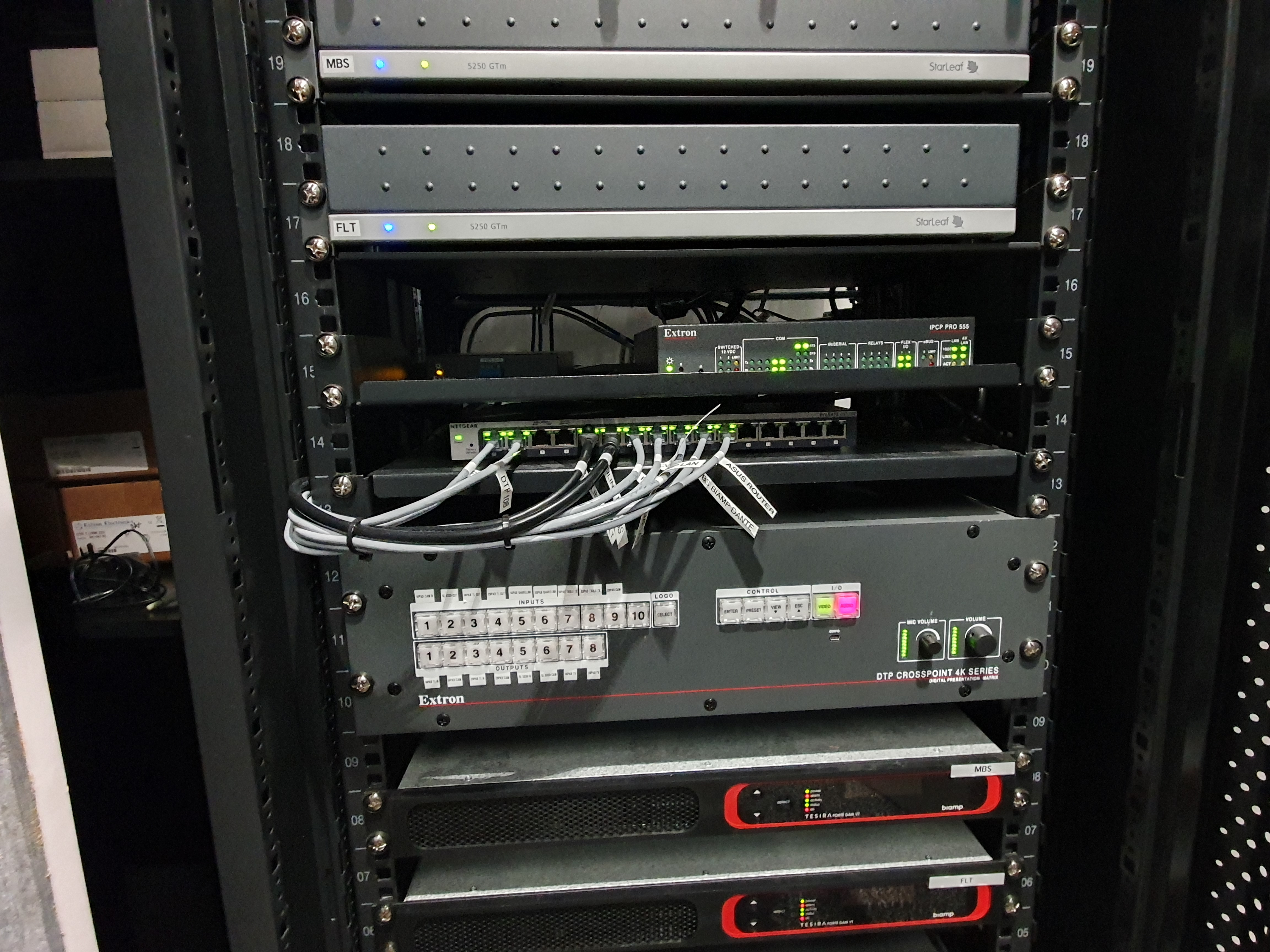 A DTP CrossPoint 108 4K scaling presentation matrix switcher rack-mounted in a back corner of the 20-seat conference room provides AV and control signal routing within both it and the 14-seat conference room.