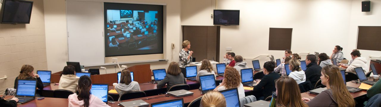 Classroom with teacher lecturing and students viewing projector screen