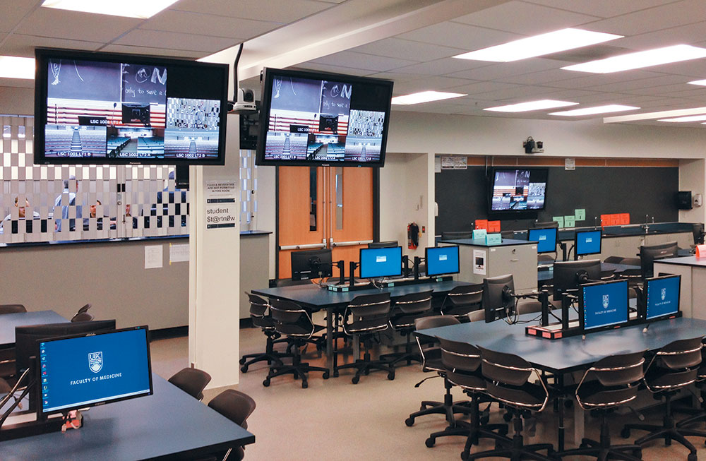 Each two-seat dry lab station includes two displays and a gooseneck microphone, allowing students to ask questions in real time.