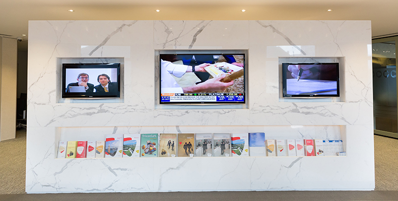 Flat panels within the reception area on Level 54 display company and product information for visitors.
