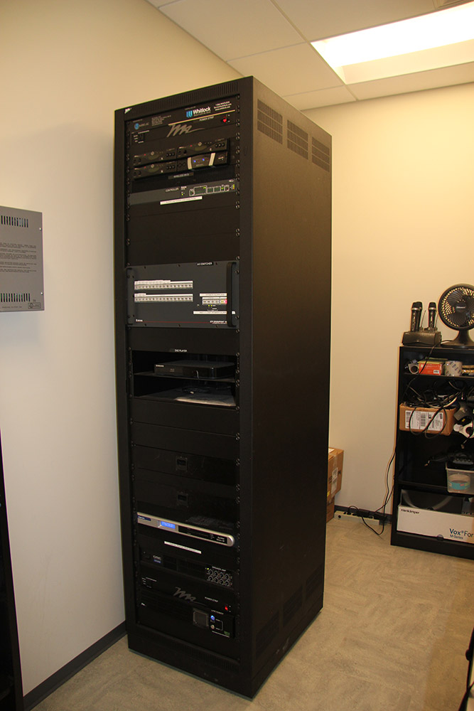 The XTP CrossPoint and shared resources are rack mounted within an equipment room adjacent to the pre-function area.
