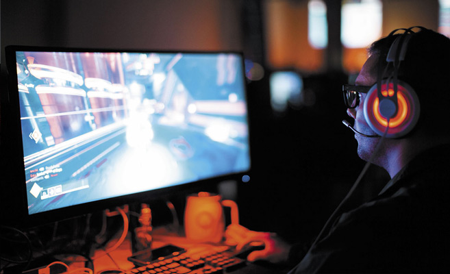 A man playing a video game on a desktop computer.