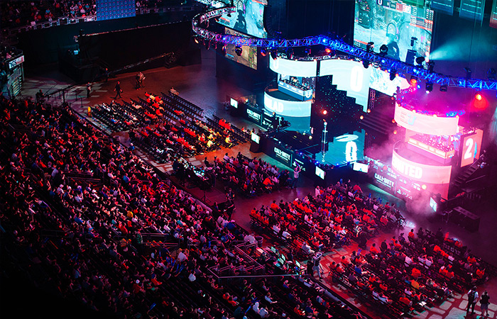 An aerial view of an Esports arena, and all of the screens surrounding the stage.