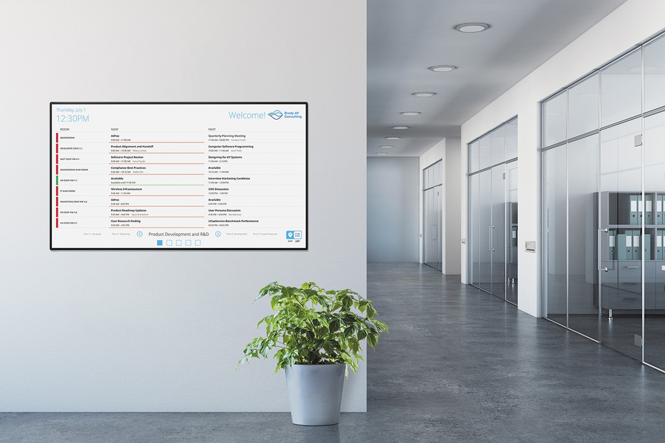 Extron Room Scheduling panel in an interactive list view placed on an office wall.